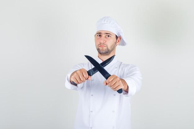 Chef masculino segurando facas cruzadas em uniforme branco e olhando sério.