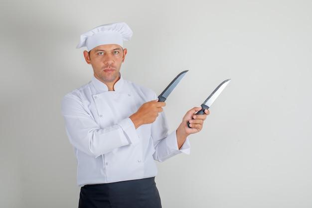 Chef masculino segurando facas de cozinha em uniforme, chapéu e avental