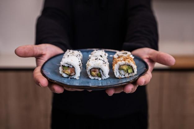 Chef masculino segurando o prato azul de sushi roll em uma cozinha.