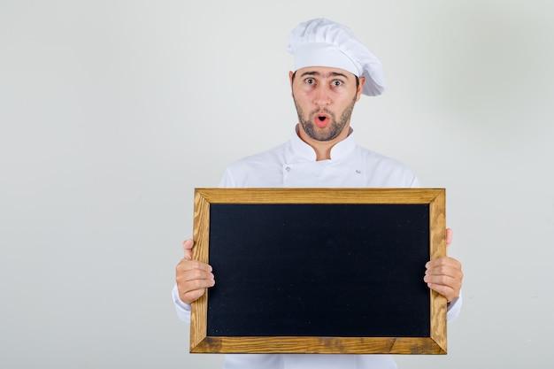 Chef masculino segurando uma lousa em uniforme branco e parecendo chocado