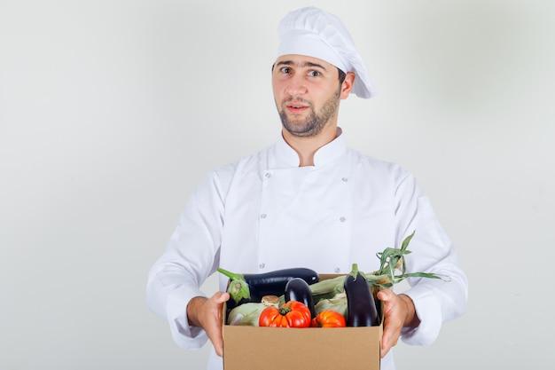 Chef masculino segurando vegetais na caixa em uniforme branco e parecendo alegre.