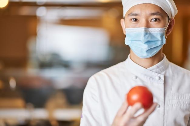 Chef masculino sério posando com tomate fresco maduro