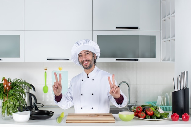 Chef masculino sorridente com chapéu de cozinheiro fazendo sinal de vitória em pé atrás da mesa da cozinha.
