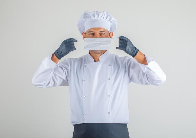 Chef masculino vestindo máscara médica em uniforme, avental e chapéu e olhar cuidadoso