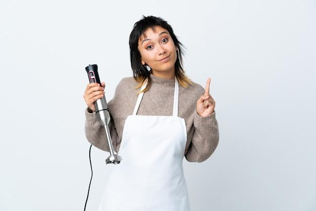 Chef menina usando liquidificador mão sobre isolado branco apontando com o dedo indicador uma ótima idéia