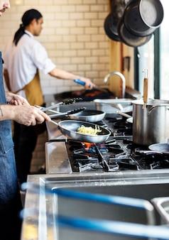 Chef, mexendo um espaguete em uma estação de wok