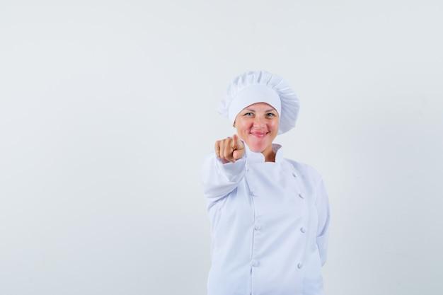 Chef mulher apontando para a frente com uniforme branco e parecendo feliz