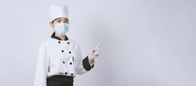 Chef mulher asiática em uniforme de cor branca com produtos higiênicos, como máscara facial médica e mãos de borracha