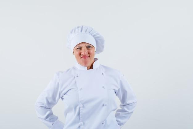 Chef mulher azedando o rosto enquanto olha para a frente em uniforme branco e parece insatisfeito.