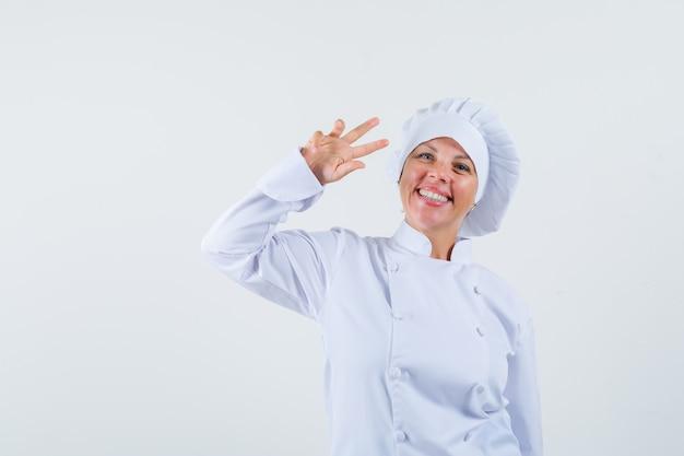 Chef mulher com uniforme branco mostrando o sinal em v e parecendo alegre