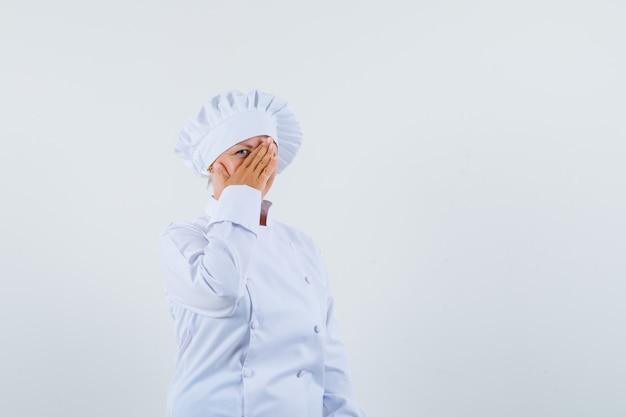 Chef mulher de uniforme branco olhando por cima da mão e escondida