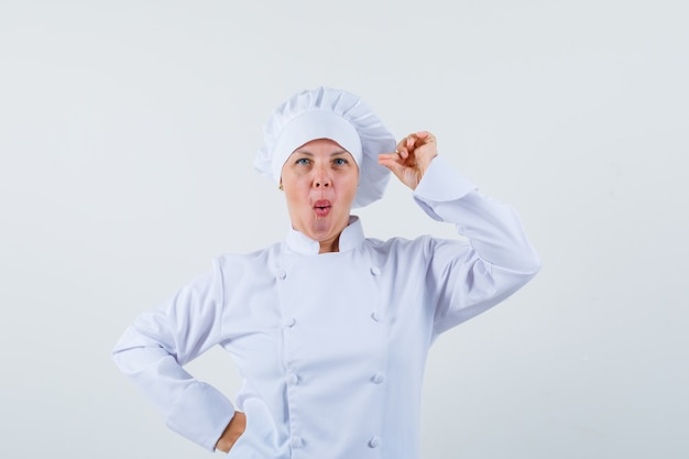 Chef mulher em uniforme branco posando enquanto faz beicinho e parece focado
