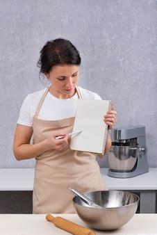 Chef mulher está segurando um livro de receitas na cozinha, segurando uma aula de culinária. quadro vertical.