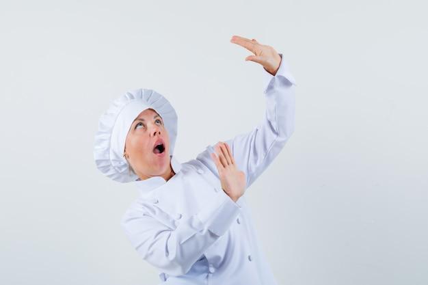 Chef mulher levantando as mãos para se defender com uniforme branco e parecendo assustada