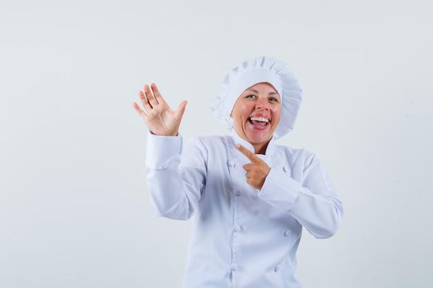 Chef mulher posando como se estivesse apontando para algo em sua mão com uniforme branco e parecendo feliz