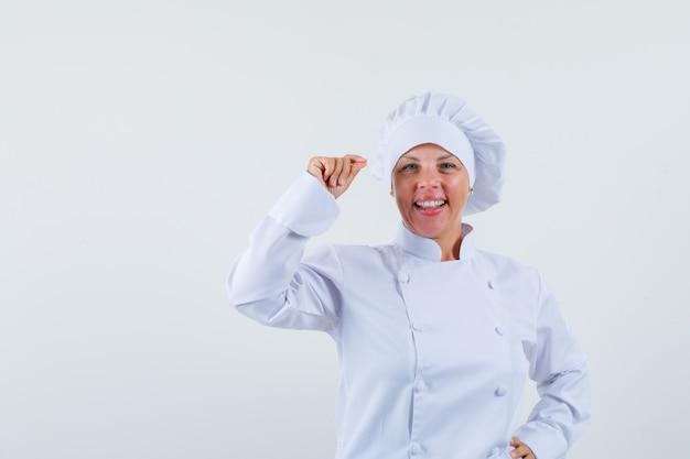 Chef mulher posando segurando algo em um uniforme branco e parecendo feliz