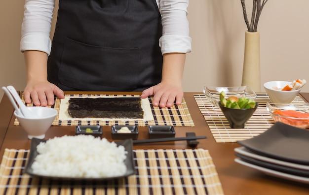 Chef mulher pronta para preparar rolos de sushi japoneses, com os principais ingredientes em primeiro plano. foco seletivo em algas nori