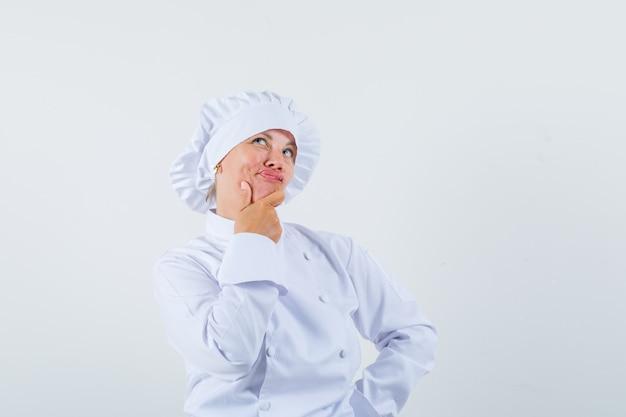 Chef mulher segurando a mão no queixo em uniforme branco e parecendo hesitante.