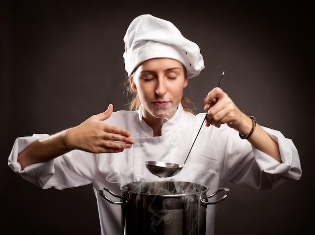 Chef mulher segurando uma concha e cheirando