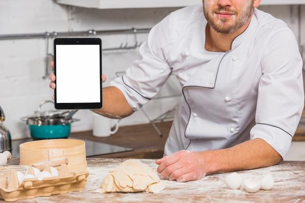 Chef na cozinha com modelo de tela do tablet