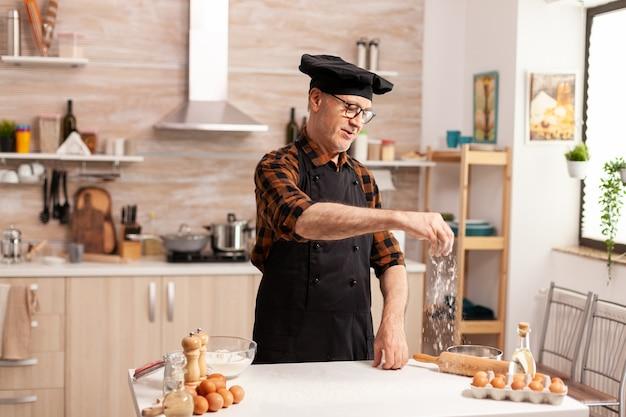Chef na cozinha de casa massa sem glúten para massas, padarias ou pizzas. chef sênior aposentado com bonete e avental, em uniforme de cozinha, polvilhando ingredientes peneirados com a mão.