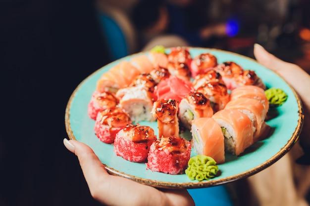 Chef na cozinha do hotel ou restaurante decorando saborosos rolos com maionese japonesa em garrafa. preparando o conjunto de sushi. apenas mãos.