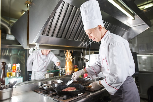 Chef na cozinha do restaurante no fogão com panela, cozinhar