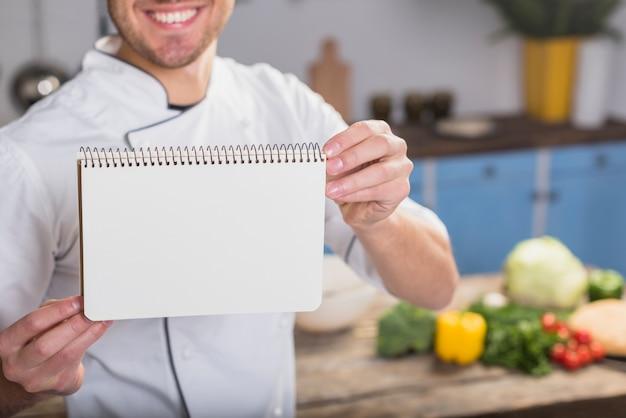 Chef na cozinha mostrando o bloco de notas