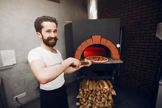Chef na cozinha prepara pizza
