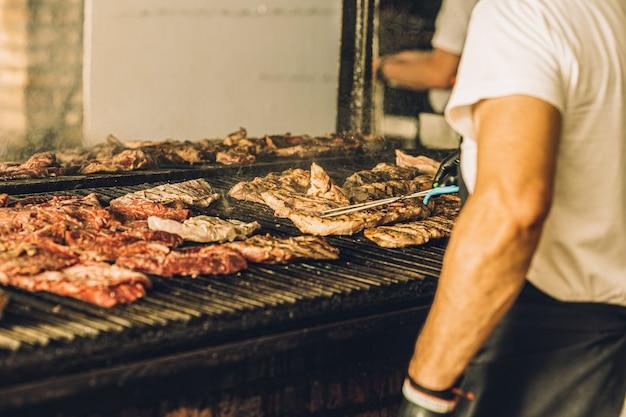 Chef não reconhecido usando luvas para cozinhar bife na grelha e usando pinças de carne.