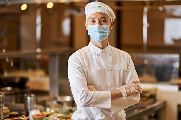 Chef orgulhoso posando em seu local de trabalho perto dos utensílios de cozinha