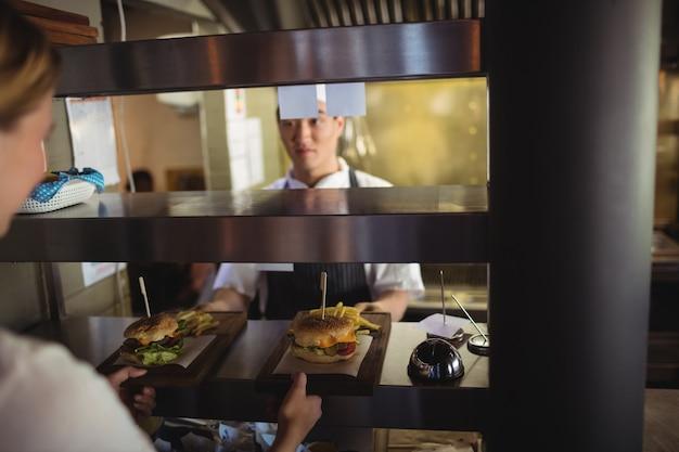 Chef passando bandeja com batatas fritas e hambúrguer para a garçonete