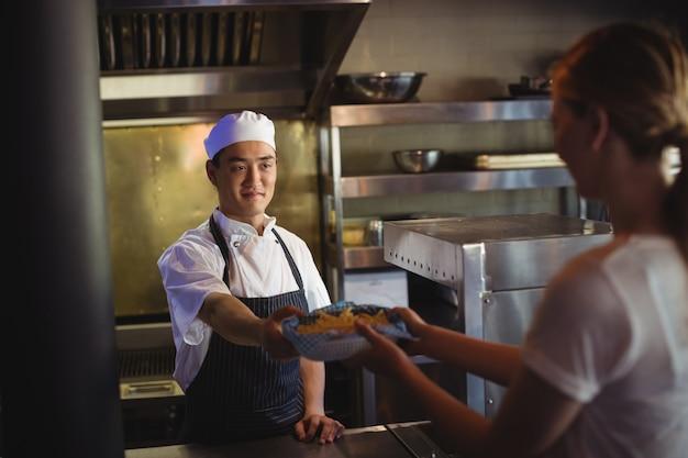 Chef passando bandeja com batatas fritas para a garçonete