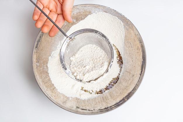 Chef peneirando farinha na peneira