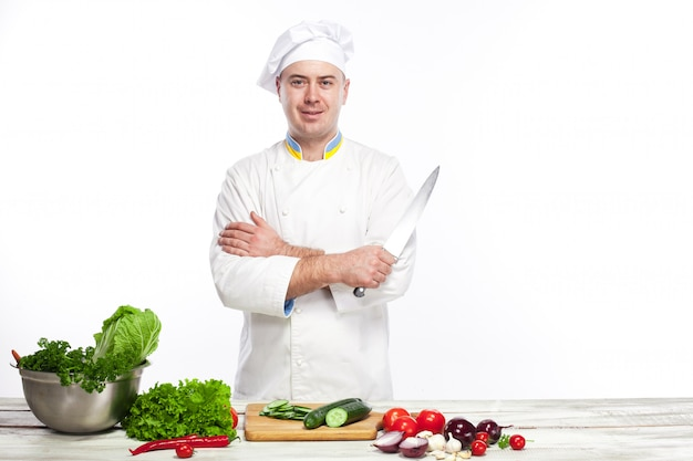 Chef posando com faca em sua cozinha