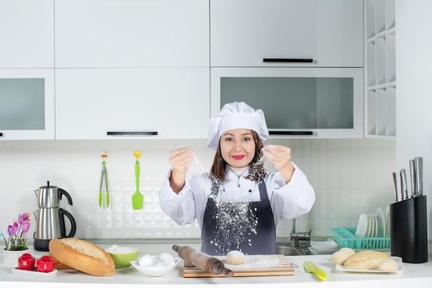 Chef positiva do commis feminino de uniforme em pé atrás da mesa, manchando o rosto com farinha na cozinha branca