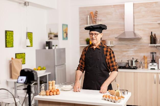Chef positivo gravando na cozinha uma nova receita para o canal de vídeo. influenciador padeiro blogueiro aposentado que usa tecnologia da internet para se comunicar, atirar e fazer blogs nas redes sociais com equipamento digital