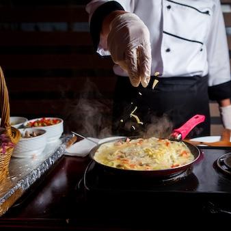 Chef prepara deliciosa refeição em uma vista lateral de cozinha