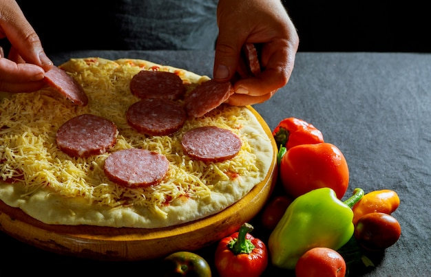 Chef prepara deliciosas pizzas, linguiça salgada, massa grossa, massa de pizza
