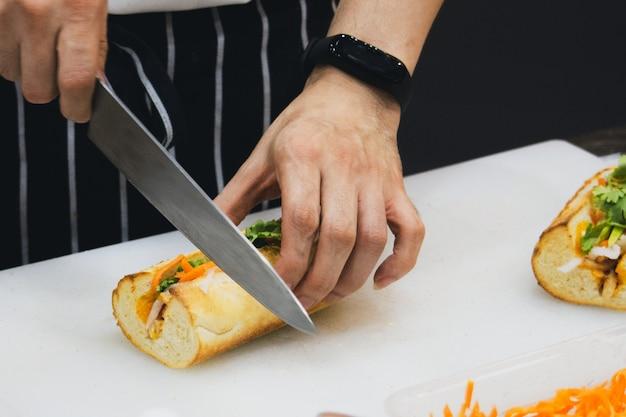 Chef prepara sanduíche na cozinha, delicioso sanduíche com legumes e carne