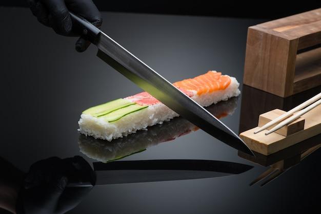 Chef prepara sushi, corta com uma faca. sushi em fundo preto com reflexo