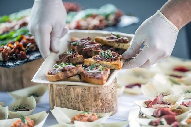 Chef preparando mini pães tártaro de carne crua em um evento de catering.