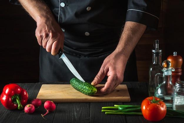 Chef profissional corta pepino verde na mesa da cozinha do restaurante para salada. dieta vegetal ou ideia de lanche.