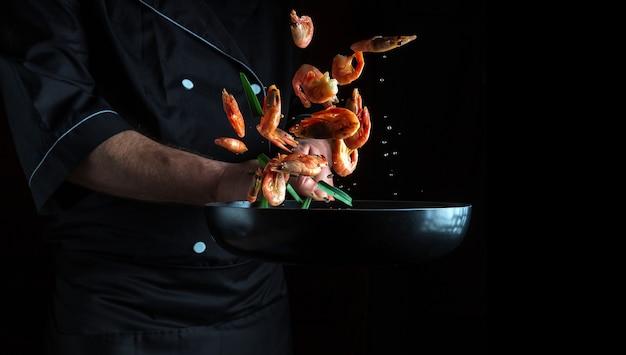 Chef profissional cozinha camarão em uma panela com vegetais congelando em movimento espaço de publicidade gratuito