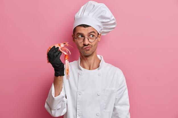Chef profissional cozinha frutos do mar, comida vegetariana saudável, segura lagostins e usa uniforme branco de cozinheiro