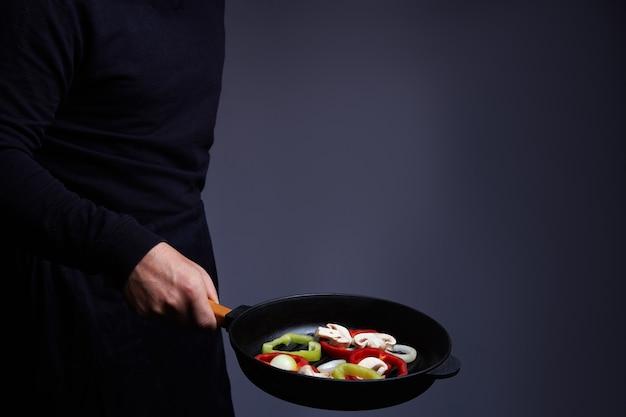 Chef profissional. cozinha vegetais em uma panela, culinária asiática. comida deliciosa e saudável
