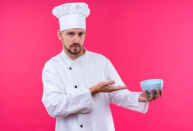 Chef profissional cozinheiro de uniforme branco e chapéu de cozinheiro, apresentando uma tigela com o braço da mão em pé sobre um fundo rosa