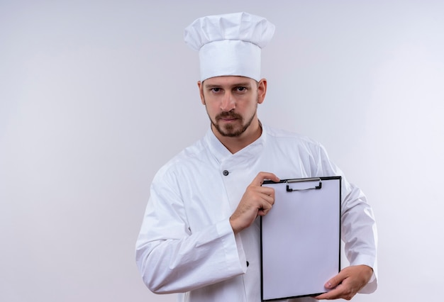 Chef profissional cozinheiro de uniforme branco e chapéu de cozinheiro demonstrando a prancheta com páginas em branco sobre fundo branco