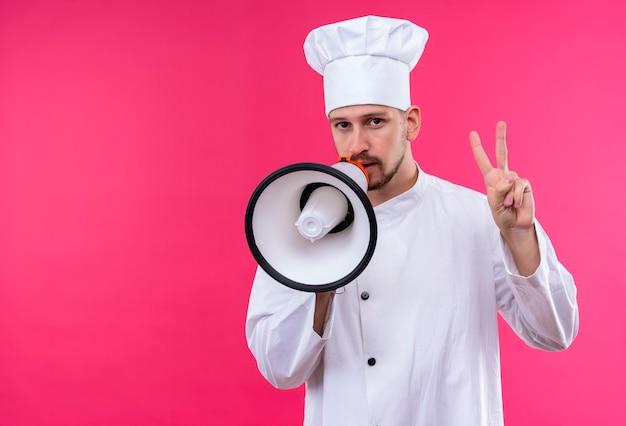 Chef profissional cozinheiro de uniforme branco e chapéu de cozinheiro falando para o megafone, mostrando o número dois em pé sobre um fundo rosa