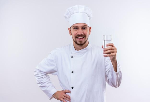 Chef profissional cozinheiro de uniforme branco e chapéu de cozinheiro segurando um copo d'água sorrindo alegremente em pé sobre um fundo branco